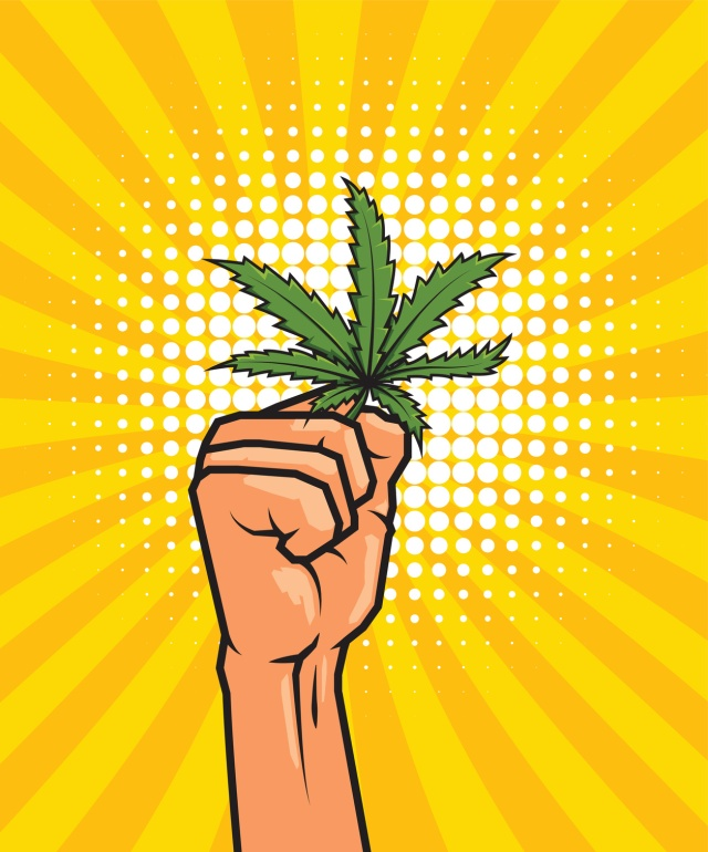 Fist held high hold on cannabis leaf.